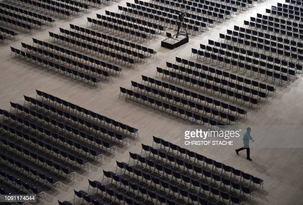 TOPSHOT An employee walks between seats ahead of the Siemens company's annual shareholder's meeting in the Olympic hall in Munich southern Germany on...