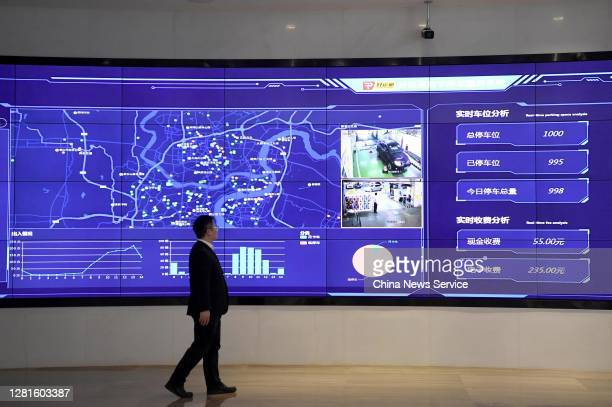 An employee walks by a screen displaying real-time parking space analysis based on the Chongqing New Type Internet of Things Big Data Service...
