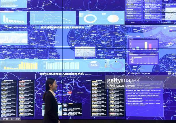 An employee walks by a screen displaying real-time traffic information based on the Chongqing New Type Internet of Things Big Data Service Platform...