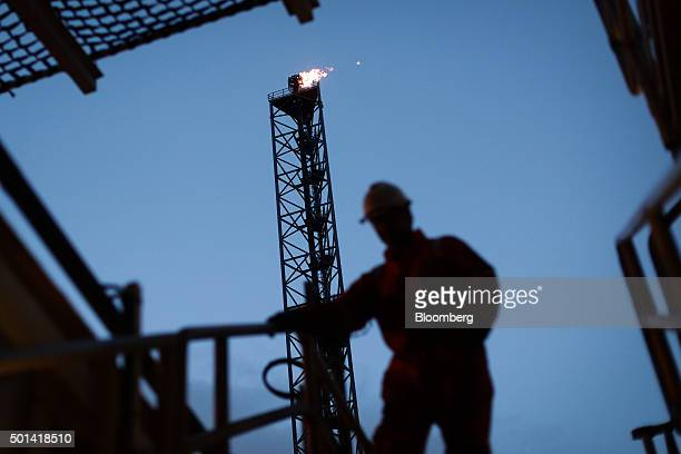 An employee walks down stairs in view of a gas burn off venting pipe on the Armada gas condensate platform, operated by BG Group Plc, in the North...