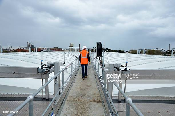 An employee walks down the central walkway between selfsupporting seals that trap odor from wastewater taken from the neighboring Shell Australia Ltd...