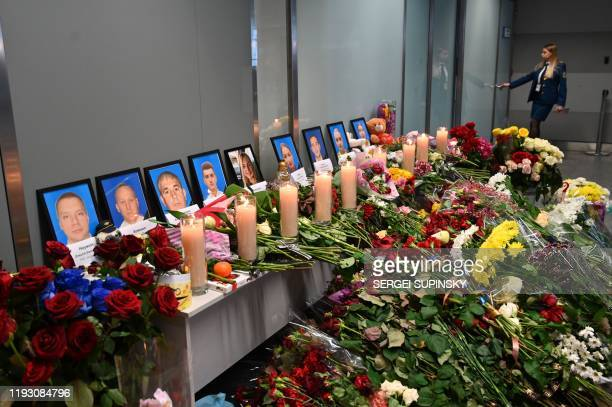 An employee walks in background of a makeshift memorial set up for the victims of the Ukraine International Airlines Boeing 737800 that crashed near...