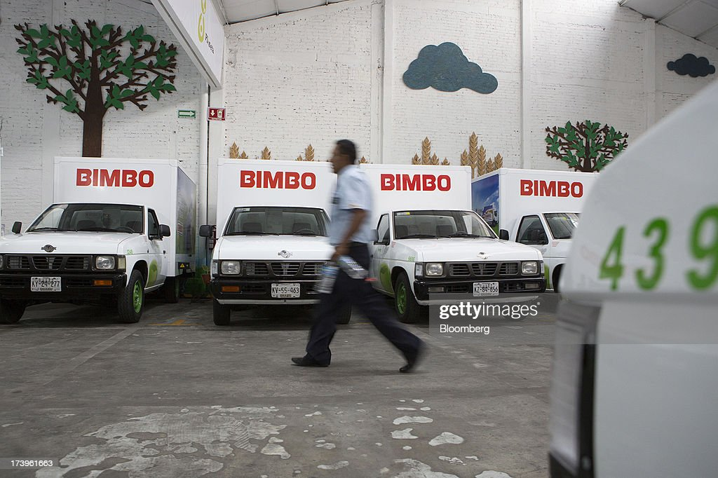 An employee walks in front of electric delivery trucks inside Grupo Bimbo SAB de CV's new sales center in Mexico City, Mexico, on Thursday, July 18, 2013. Grupo Bimbo inaugurated a new eco-friendly sales center today. Photographer: Susana Gonzalez/Bloomberg via Getty Images