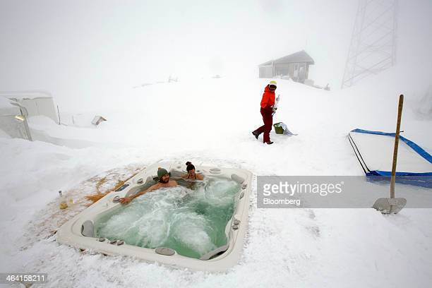 An employee walks in the snow past guests as they relax in an outdoor hot tub at the igloo hotel operated by IgluDorf GmbH on the Parsenn mountain in...