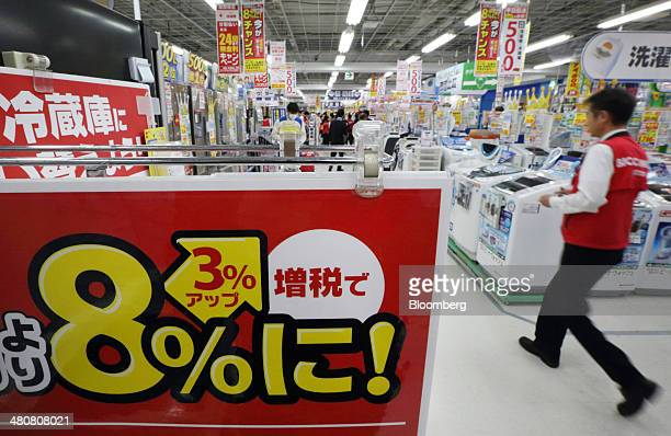 An employee walks near a sign indicating consumption tax will be raised to 8 percent at a Bic Camera Inc electronics store in Tokyo Japan on Thursday...