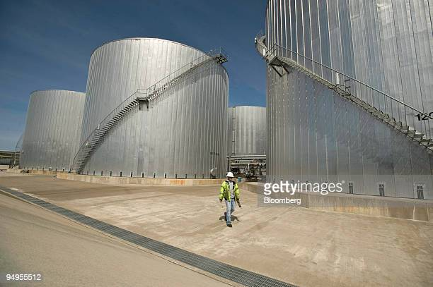 An employee walks near storage tanks at the Imperium Grays Harbor LLC biodiesel plant in Aberdeen, Washington, U.S., on Friday, May 15, 2009. The...