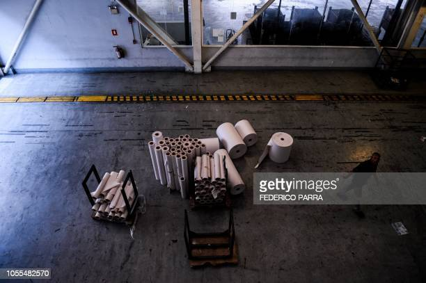 An employee walks next to remaining paper rolls at the printing room of Venezuelan newspaper El Nacional in Caracas on October 5 2018 Surrounded by...