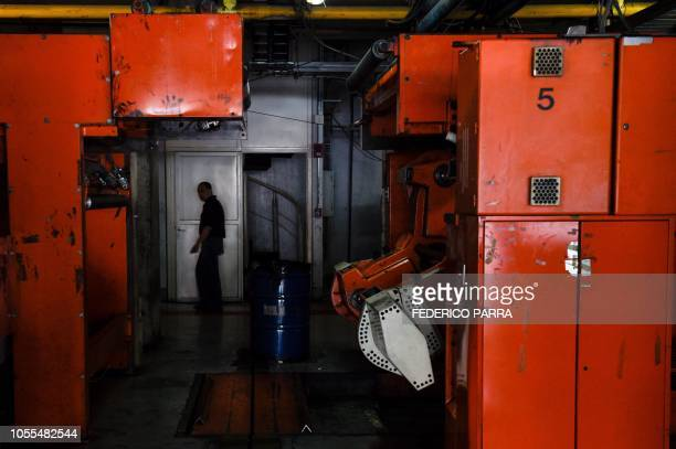 An employee walks next to the printing press Venezuelan newspaper El Nacional in Caracas on October 5 2018 Surrounded by empty chairs a bunch of...