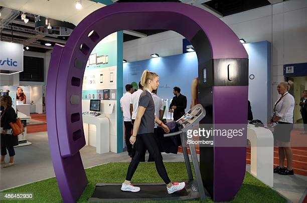 An employee walks on a treadmill inside a giant replica Fitbit Inc watch during the IFA International Consumer Electronics Show in Berlin Germany on...