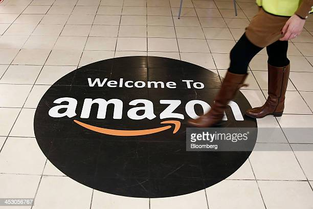 An employee walks over a logo on the floor of Amazoncom Inc's fulfillment centers in Rugeley UK on Monday Dec 2 2013 Online retailers in the UK are...