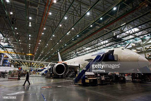 An employee walks past a Boeing Co 787 Dreamliner during final assembly of the airplane at the Boeing Co factory in Everett Washington US on Tuesday...