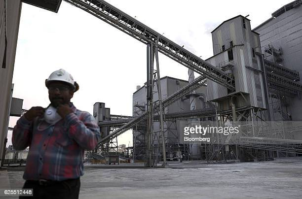 An employee walks past a conveyor system carrying diammonium phospate to the processing plant at the Ras Al Khair Industrial City operated by the...