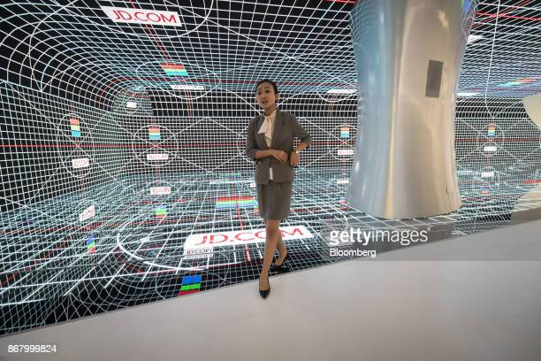 An employee walks past a digital screen at a showroom inside the JDcom Inc headquarters in Beijing China on Monday Oct 23 2017 JDcom isChina's...