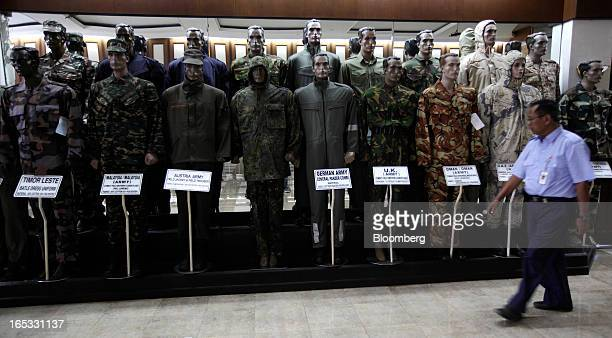 An employee walks past a display of military uniforms of various countries in the showroom at a PT Sri Rejeki Isman factory in Sukoharjo Java...