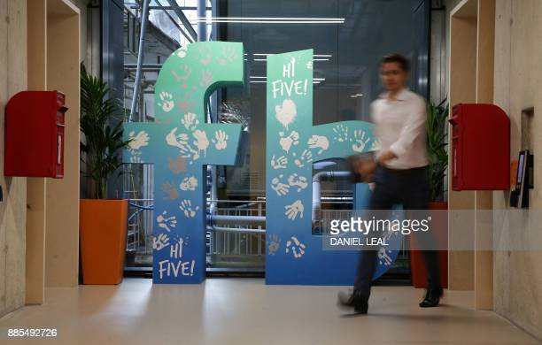 An employee walks past a Facebook logo at Facebook's new headquarters, designed by Canadian-born American architect Frank Gehry, at Rathbone Place in...