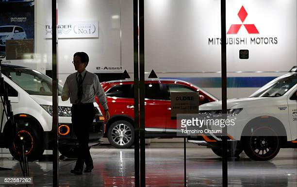 An employee walks past a Mitsubishi Motors vehicles displayed at the company's headquarters on April 20 2016 in Tokyo Japan Mitsubishi Motors share...