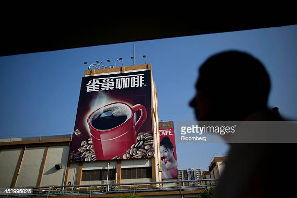 An employee walks past a Nestle SA Nescafe Coffee billboard advertisement at the Nestle Dongguan Ltd factory in Dongguan Guangdong province China on...