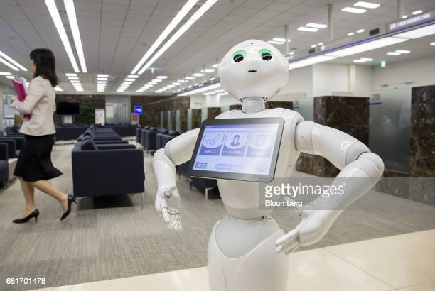 An employee walks past a Pepper humanoid robot developed SoftBank Group Corp at the Mizuho Bank Ltd branch inside the Mizuho Financial Group Inc...