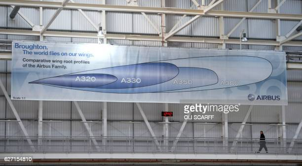 An employee walks past a poster comparing the size of wing crosssections for various Airbus aircraft in the Airbus A350 wing production plant near...