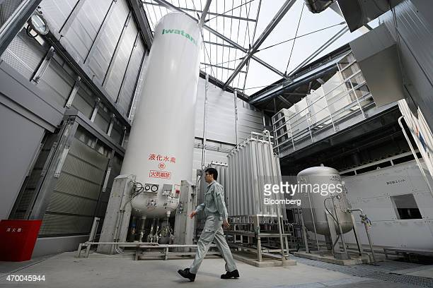 An employee walks past a storage tank at an Iwatani Corp hydrogen fueling station in Tokyo Japan on Friday April 17 2015 Toyota Motor Corp the...