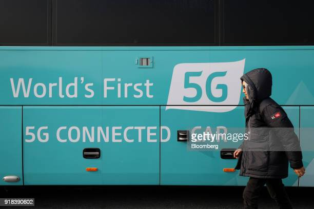 An employee walks past an autonomous 5G connected bus operated by KT Corp during a media event in Gangneung Gangwon Province South Korea on Wednesday...