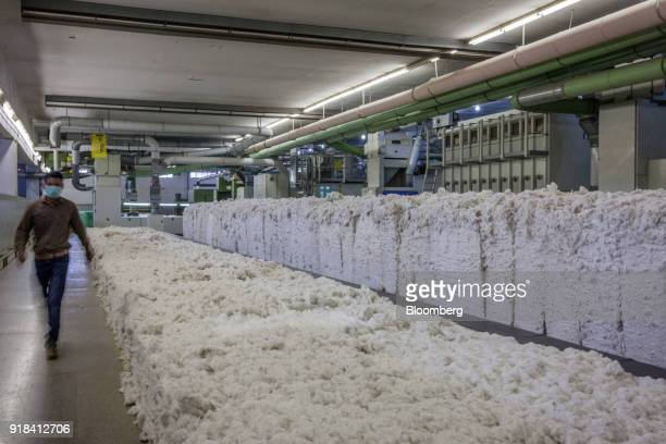 An employee walks past batches of blended cotton inside a blowroom unit at the Artistic Denim Mills Ltd factory in Karachi Pakistan on Tuesday Feb 6...