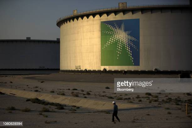 An employee walks past crude oil storage tanks at the Juaymah Tank Farm in Saudi Aramco's Ras Tanura oil refinery and oil terminal in Ras Tanura...