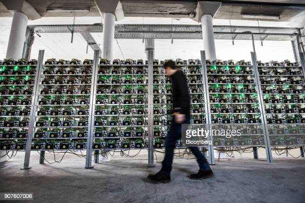An employee walks past cryptocurrency mining rigs composed of Antminer S9 ASIC machines on racks at the HydroMiner GmbH cryptocurrency mining...