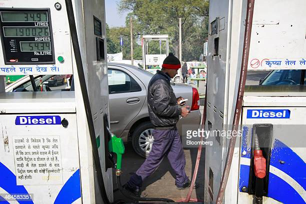 An employee walks past diesel gas pumps at a Hindustan Petroleum Corp gas station in New Delhi India on Monday Jan 20 2014 India China and Brazil...