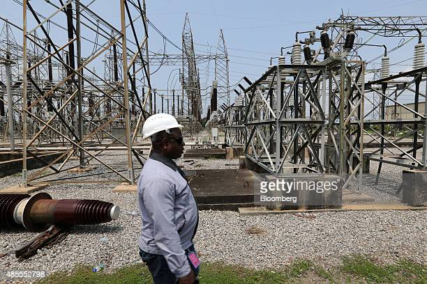 An employee walks past electricity pylons carrying high voltage cables at the newly renovated energy generation plant operated by Egbin Power Plc in...
