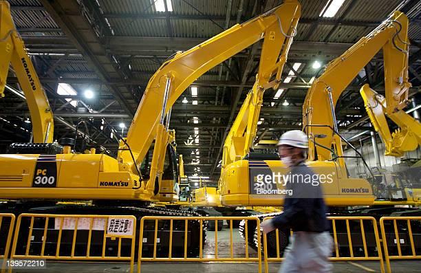 An employee walks past Komatsu Ltd excavators on the production line of the company's plant in Hirakata City Osaka Japan on Thursday Feb 23 2012...