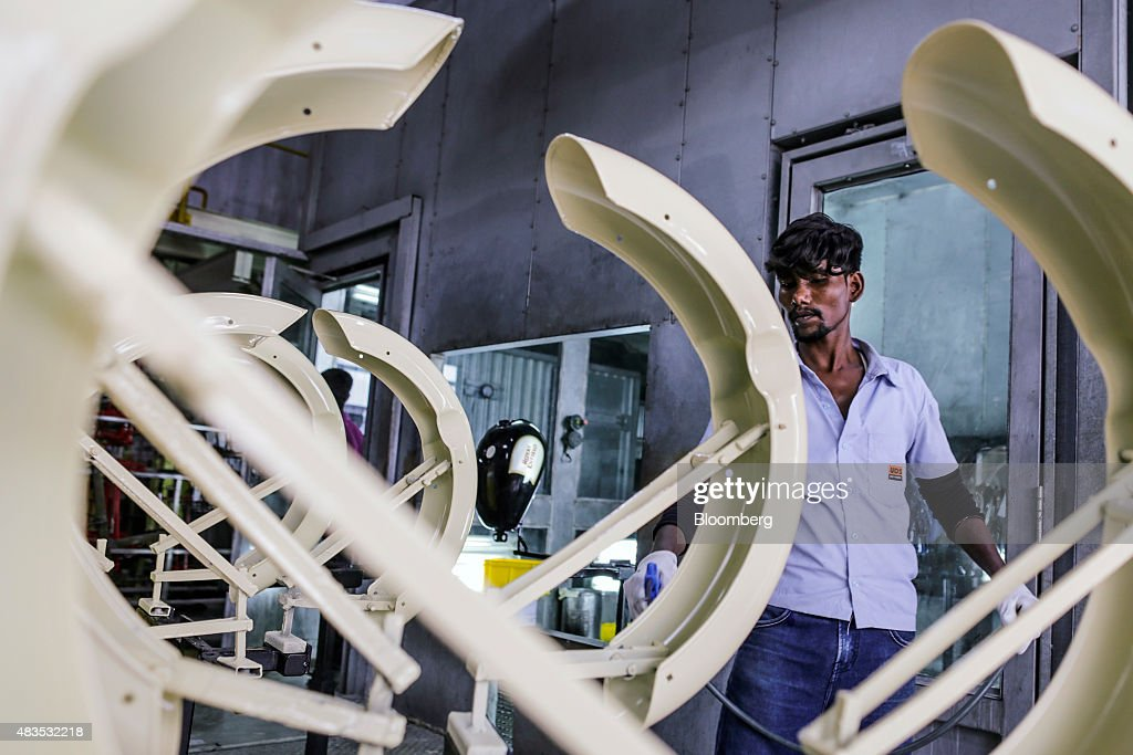 An employee walks past mud guards for the Royal Enfield Motors Ltd Classic 5000 motorcycle as they move on a conveyor on the production line at the...