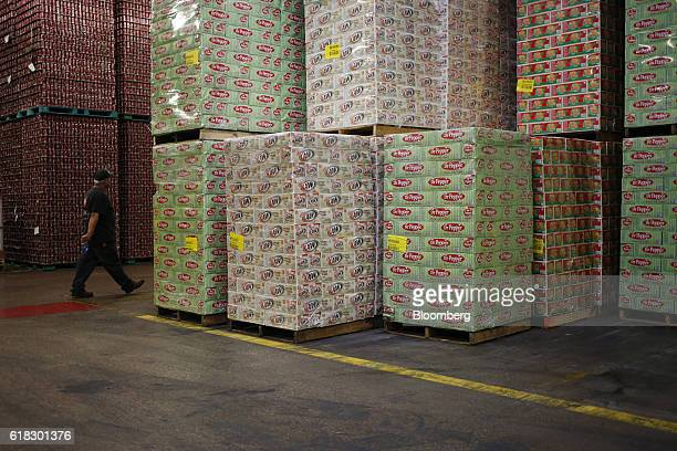An employee walks past pallets of Dr Pepper Snapple Group Inc brand sodas at the company's bottling plant in Irving Texas US on Tuesday Oct 25 2016...
