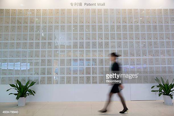 An employee walks past patent certificates displayed on a wall inside an exhibition hall at the Huawei Technologies Co campus in the Longgang...