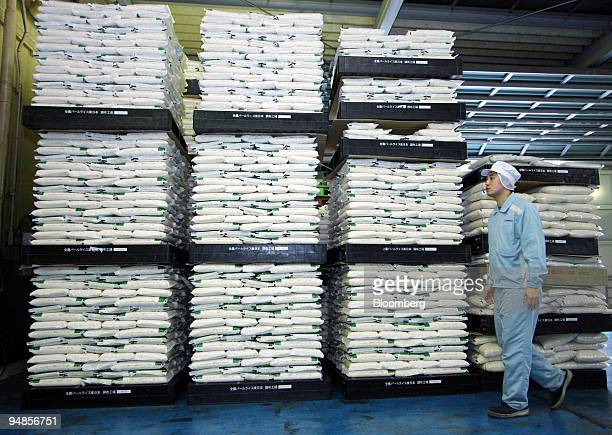 An employee walks past sacks of rice at Zennoh Pearl Rice Corp's Chofu rice polishing plant in Tokyo Japan on Monday April 14 2008 As developing...