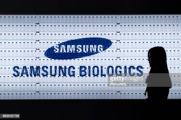 An employee walks past Samsung BioLogics Co. Signage seen behind medicine bottles on display at the company's headquarters and production facilities...