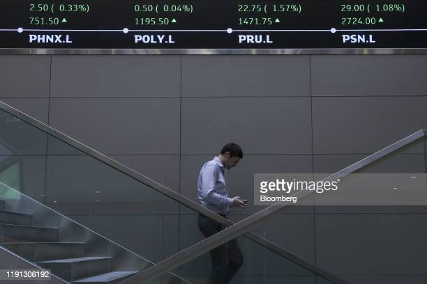 An employee walks past share price information for tickers listed on the FTSE100 share price index in the atrium of the London Stock Exchange Group...