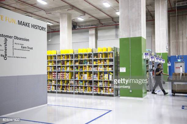 An employee walks past shelves filled with merchandise at Amazoncom Inc's Amazon Prime Now fulfillment center in Singapore on Thursday July 27 2017...