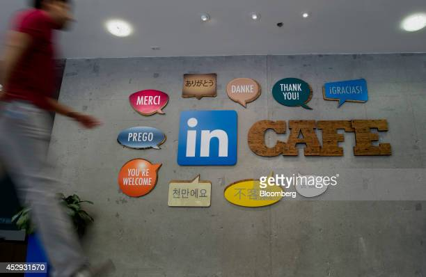 An employee walks past signs displayed on the wall outside one of the lunchrooms at LinkedIn Corp headquarters in Mountain View California US on...