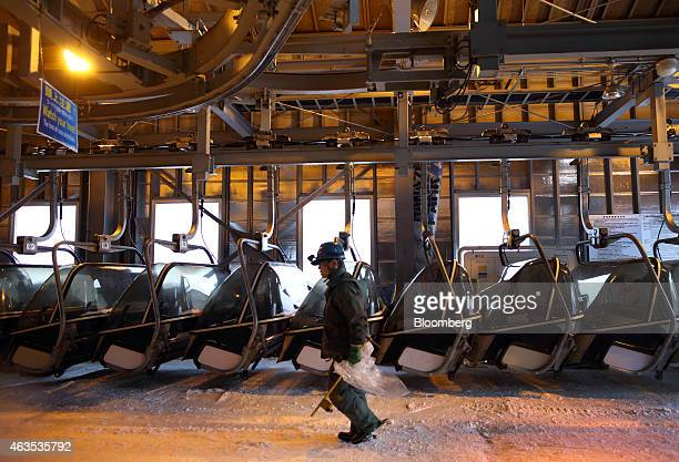 An employee walks past ski lifts ahead of the day's operation at the Niseko Hanazono resort operated by Nihon Harmony Resorts KK in Kutchan Hokkaido...