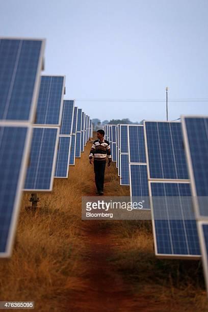 An employee walks past solar panels at the Welspun Energy Ltd solar power plant in Neemuch Madhya Pradesh India on Wednesday Feb 26 2014 Welspun...