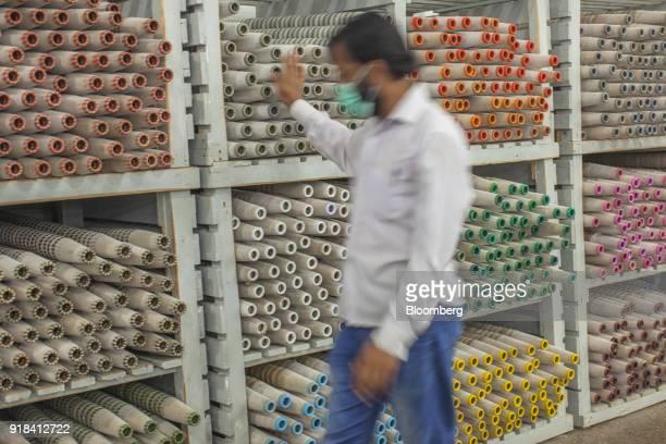 An employee walks past stacks of cotton yarn bobbins inside the carding unit at the Artistic Denim Mills Ltd factory in Karachi Pakistan on Tuesday...