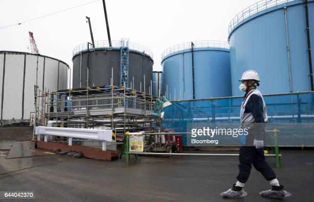 An employee walks past storage tanks for contaminated water at Tokyo Electric Power Co's Fukushima Daiichi nuclear power plant in Okuma Fukushima...