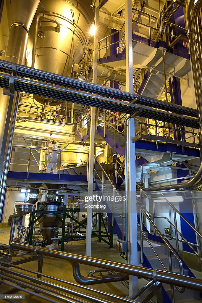 An employee walks past tanks and pipes inside Synlait Milk Ltd.'s manufacturing plant in the town of Rakaia, 60km from Christchurch, New Zealand, on Friday, Aug. 30, 2013. Synlait, a unit of Shanghai-based Bright Dairy & Food Co., will process more milk than forecast in 2013-14, the company announced on Aug. 30. Photographer: Brendon O'Hagan/Bloomberg via Getty Images