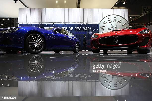 An employee walks past the Maserati Ghibli left and GranTurismo vehicles produced by Fiat SpA during the press day of the Seoul Motor Show in Goyang...