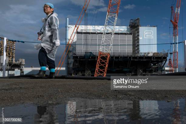 An employee walks past the Unit 2 reactor building at Tokyo Electric Power Co.'s Fukushima Dai-ichi nuclear power plant on January 29, 2020 in Okuma,...