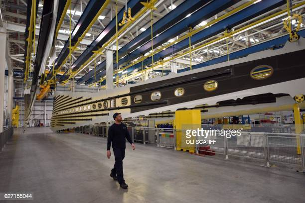An employee walks past top and bottom panels for the wings of an Airbus A350 aircraft at Airbus' wing production plant near Broughton in northeast...
