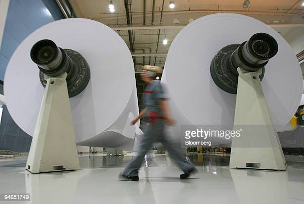 An employee walks past two paper reels at the Stora Enso paper mill in Oulu Finland Monday Aug 13 2007 Stora Enso Oyj the world's largest paper maker...
