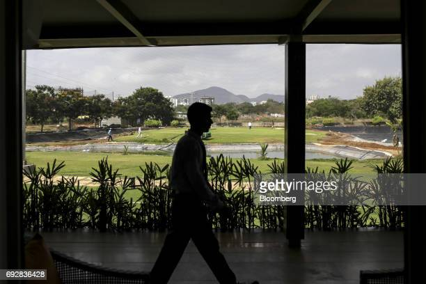 An employee walks though a golf club in Palava City on the outskirts of Mumbai India on Thursday May 25 2017 Lodha Group best known for its luxury...