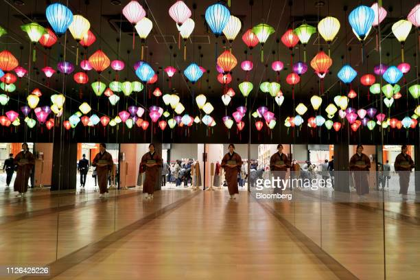 An employee walks through a corridor decorated with lantern-shaped lights inside the Solaniwa Onsen spa at Osaka Bay Tower during a media tour in...